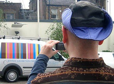 Seen from behind, I photograph a colourful minivan as I wear my purple hat and striped shirt