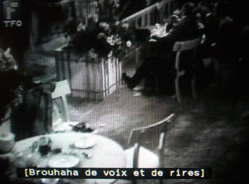 Black-and-white still frame with French caption reading [Brouhaha de voix et de rirres]