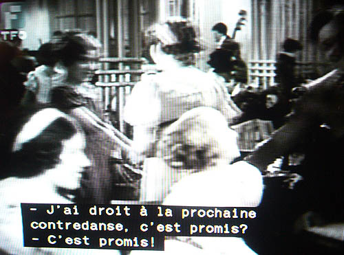 Black-and-white still frame with three lines of French dialogue